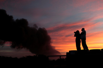 People take pictures of an explosion caused by a fire at a fuel storage tank belonging to the Puma Energy company in Puerto Sandino
