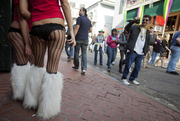 A man photographs Mardi Gras participants on Bourbon Street as part of celebrations in the French Quarter of New Orleans