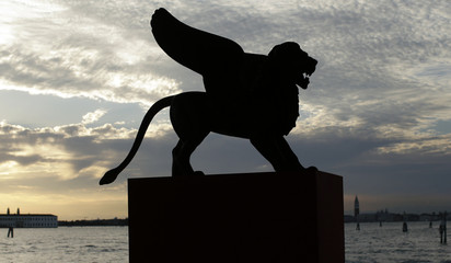 A statue of a lion, the symbol of the 69th Venice Film Festival, is silhouetted in Venice