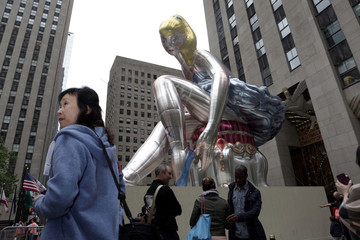 "Tourists take pictures in front of Jeff Koons' public installation ""Seated Ballerina"" in Rockefeller Center, New York City"