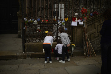 Children look at flowers placed in memory of victims of Wednesday's train crash, in front of the cathedral of Santiago de Compostela