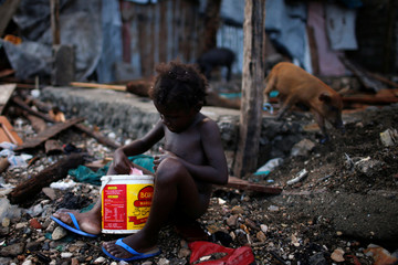 A girl takes a bath next to destroyed houses, after Hurricane Matthew hit Jeremie