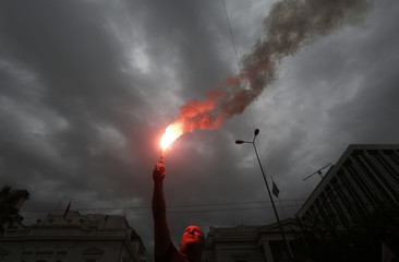 A coast guard officer waves a red flare outside the parliament as he takes part in an anti-austerity protest in Athens