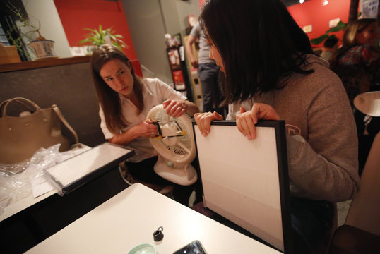 Women assemble a home made air purifier during a workshop organized by Smart Air Filters at a local coffee shop in Shanghai