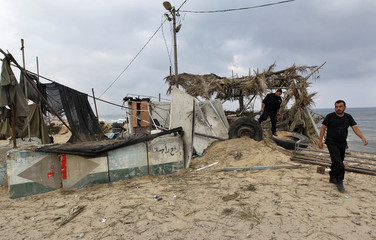 Members of Hamas's security forces walk on a Hamas compound damaged after an Israeli air strike in Gaza Strip