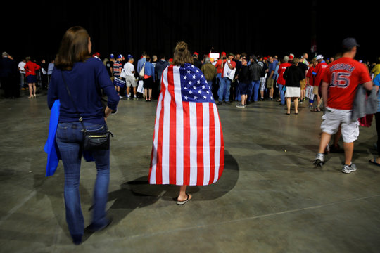 A woman wearing a U.S. flag as a cape arrives for a campaign rally with U.S. Republican presidential candidate Donald Trump in Bangor