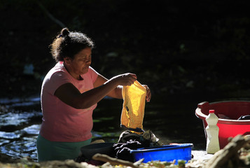 Cristina Ordonez, the widow of Alejandro Amador, washes clothes in the Chipaska river in the village La Isla (The Island) in Chichigalpa
