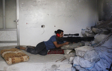 A Free Syrian Army fighter aims his weapon as he takes a defensive position in Aleppo's Karm al-Jabal district