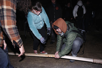 A group of Occupy Oakland protesters connect a beam to prop up a tarp to prevent rainwater from collecting and spilling on people, at a vacant lot and an adjacent park in Oakland