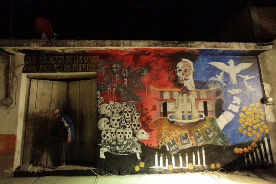 Man leaves his house, which was decorated with a mural by students, in the town of Tixtla