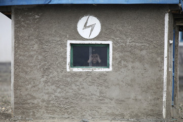 A North Korean soldier looks out of the window of a guard tower, on the banks of Yalu River