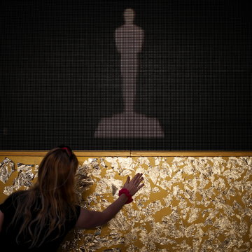 A woman applies gold leaf as decoration outside the Dolby Theatre ahead of the 88th Academy Awards in Hollywood, California