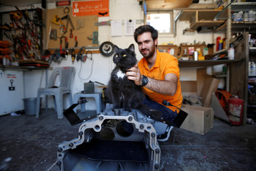 Jordanian graphic designer Abdelrahman Asfour, who turns car parts into furniture, plays with his cat as he works at his workshop in Amman