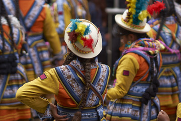 Traditional folk dancers in ornate costumes performing as they parade through the mining city of Oruro on the Altiplano of Bolivia during the annual carnival.