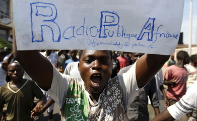 A protester carries a placard urging the government to re-open their local Radio Publique Africaine (RPA) in Burundi's capital Bujumbura