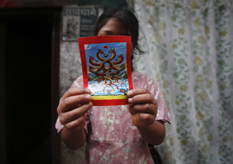 "A girl shows a picture of a snake god during the ""Nag Panchami"" festival in Kathmandu"