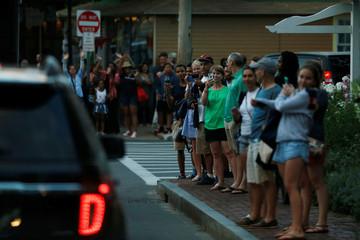 People watch President Obama's motorcade on Martha's Vineyard, Massachusetts, U.S.