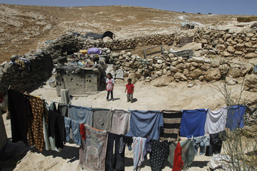 Palestinian cave dwellers stand behind a laundry line in Al-Mufaqara, near Hebron