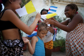 Children adorn the hair of Ana Karla, 5, with Cuban and Vatican flags as they wait for the arrival of Pope Francis from the airport in Havana