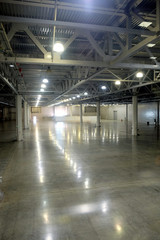 Large empty warehouse interior in an industrial building with high vertical columns with and high ceiling and artificial lighting