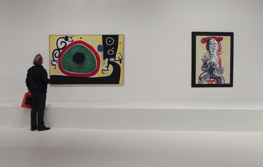 An art patron looks at Oiseaux en Fete pour le lever du Jour, 21 Mars by Joan Miro and L'Homme a la Pipe by Pablo Picasso at Art Basel in Miami Beach