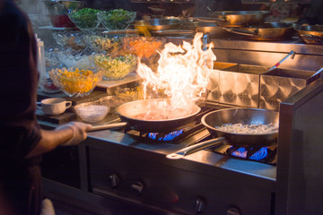 Chef in restaurant kitchen at stove with pan, doing flambe on food. low ligth selective focus.