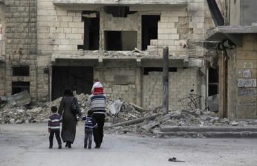 People walk along a damaged street in Aleppo's district of al-Sukari
