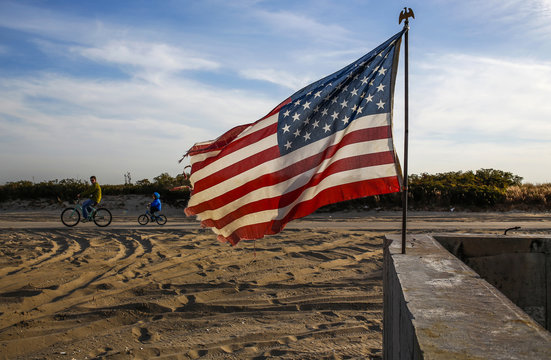 A man and child ride bikes by a land plot draped with American flags in the Breeezy Point community damaged by Hurricane Sandy in October 2012 in the borough of Queens in New York