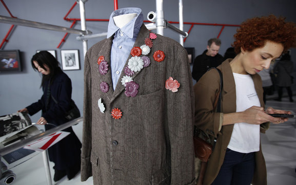 """Brown with devore floral pattern jacket and metal flower brooches"" designed by Yohji Yamamoto is displayed at the V&A in London"