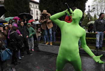 A man dressed as an invented superhero gestures during a protest against spending cuts in public education in Oviedo