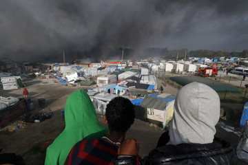 "Migrants look at burning makeshift shelters and tents in the ""Jungle"" on the third day of their evacuation as part of the dismantlement of the camp called the ""Jungle"" in Calais"