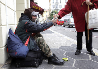 A homeless begs in a street of Nice