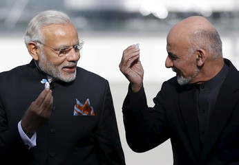 India's PM Modi and Afghanistan's President Ashraf Ghani hold sweets as they inaugurate Afghanistan's new parliament building in Kabul Afghanistan