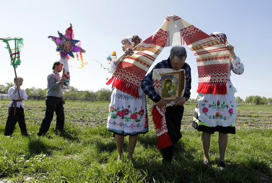 A villager walks under a scarf as he carries an icon of the Mother of God at a parade during a ritual celebrating the pagan god Yurya in Pogost