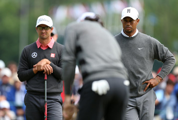 Woods of the U.S. watches Northern Ireland's McIlroy putt on the 14th green with Ausralia's Scott during the second round of the 2013 U.S. Open golf championship at the Merion Golf Club in Ardmore