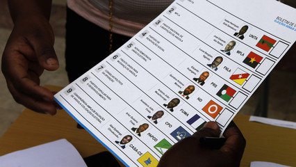 An election official hands a ballot paper to a voter during national elections in the capital Luanda