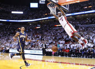 Heat's James hangs from the net after a dunk as Pacers' Hill runs back fro the ball during the third quarter in Game 5 of their NBA Eastern Conference final basketball playoff in Miami