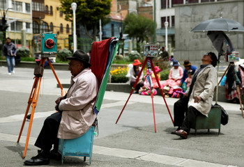 Photographers with old cameras are seen at Churubamba square in La Paz