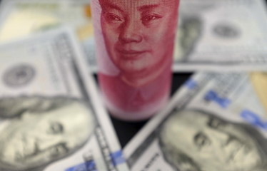 U.S. 100 dollar banknotes and a Chinese 100 yuan banknote are seen in this picture illustration in Beijing, China