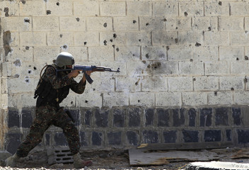 A member of Yemen's anti-terrorism unit takes his position during a training exercise near Sanaa