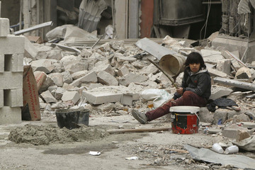 A boy sits on the rubble of buildings damaged from what activists said was shelling by forces loyal to Syria's President Assad, in Kalasa