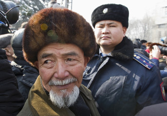 A man wearing the Kazakh national hat stands in front of a police officer during an opposition rally in Almaty