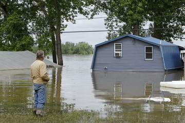 Williams checks the damage to his home and after being inundated by flood waters from the Ohio River in Kentucky