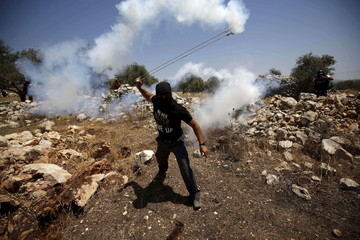 Palestinian protester uses a slingshot to return a tear gas canister fired by Israeli troops during clashes following a protest against Jewish settlements in the West Bank village of Bilin, near Ramallah