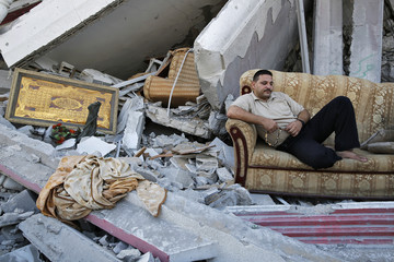 A Palestinian sits amid the ruins of destroyed homes in the Shejaia neighbourhood of Gaza City