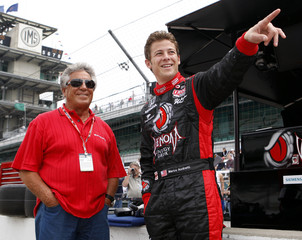 Mario and Marco Andretti watch the action in the pit lane at the Indianapolis Motor Speedway
