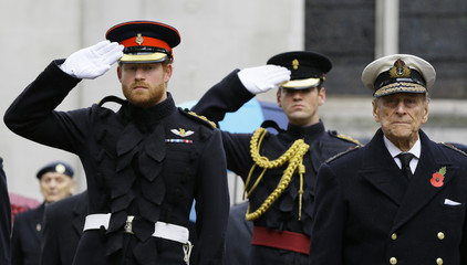 Britain's Prince Harry salutes as he stands alongside Prince Philip during a visit to the Field of Remembrance at Westminster Abbey in London