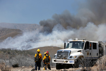 Firefighters keep watch on the Blue Cut fire burning near Wrightwood