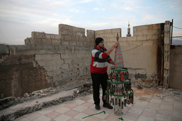 Akram Abu al-Foz, decorates a christmas tree from empty shells he collected and drew on, in the rebel held besieged city of Douma