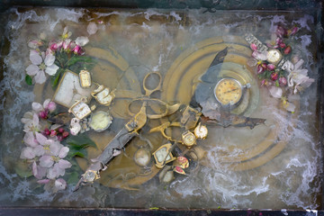 Original art still life with scissors: two pair of scissors grappled with handles and lie on a round brass plate among the flowers of an apple tree.